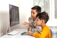 Two boys  boys doing their homework with a computer. They drawing on a computer using a tablet stock photos