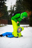 Two boys in bright winter overalls play on snow. Royalty Free Stock Photo