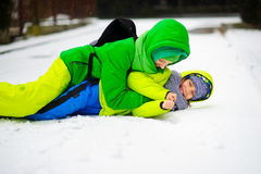 Two boys in bright winter overalls play on snow. Stock Images