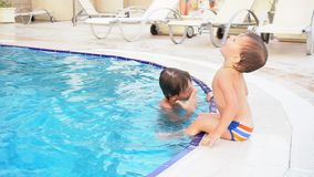 Two boys brother bathe in the swimming pool at the resort. Vacation stock video