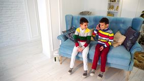 Two boys brother talks on cell phone with grandmother in turn, sitting on blue sofa in bright room during day. stock video