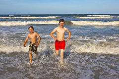 Two boys and brothers at the beach Stock Images