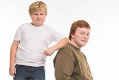 Two boys brothers and friends  studio portrait on white background playing Royalty Free Stock Image
