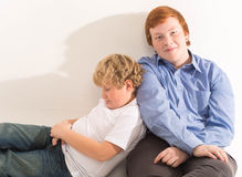 Two boys brothers and friends  studio portrait on white background playing Stock Photos