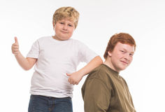 Two boys brothers and friends  studio portrait on white background playing Stock Image