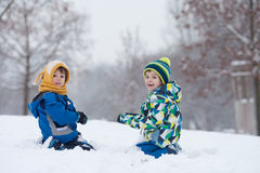 Two boys, brothers, playing in the snow with snowballs Stock Photography