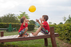 Two boys, brothers, playing with yellow balloon in the park Stock Photo