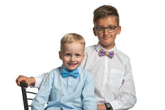 Two boys brothers sitting on a chair in shirt and butterfly isolated on white background Royalty Free Stock Image