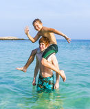 Two boys and brothers strike a funny pose in the ocean Stock Photo