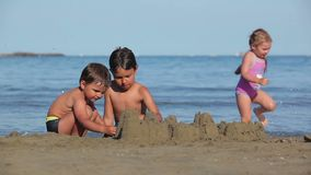 Two boys build sand castles. On the beach stock video