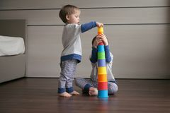 Two boys build a tower of bright glasses. royalty free stock photography