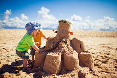 Two boys building large sandcastle on the beach Stock Images