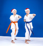 Two boys in caps of Santa Claus hit a punch arm in the rack of karate Royalty Free Stock Photos