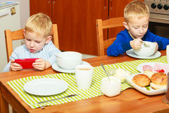 Two boys children eating breakfast at home Royalty Free Stock Photos