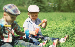 Two boys children sitting on the grass blowing soap bubbles stock photography