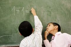 Two boys in classroom thinking, writing and counti royalty free stock image