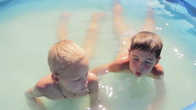 Two boys close-up of sprinkles in the pool, 1080p. Two boys  close-up of sprinkles in the pool, 1080p stock footage