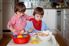 Two boys, coloring eggs for Easter at home Stock Photo