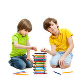 Two boys construct  a tower from pencils. Isolated on white background Stock Images