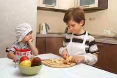 Two boys cut pear Stock Images