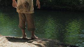 Two boys in dirty clothes and barefoot roam the riverbank. stock footage