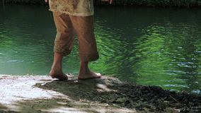 Two boys in dirty clothes and barefoot roam the riverbank. stock video footage