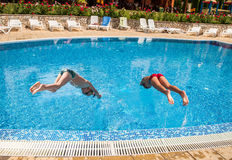 Two boys diving into a pool Stock Photo