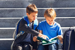 Two boys doing homework outdoors. Back to school concept. Stock Image