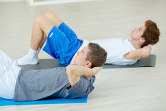 Two boys doing situp workout training in gym. Two boys doing situp workout training in the gym Stock Photo