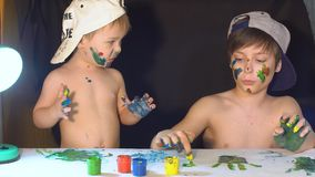 Two boys draw color paints on the paper with my fingers.  stock video