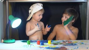 Two boys draw color paints on the paper with my fingers.  stock video footage