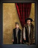 Two boys dressed as medieval lords in the wooden frame. With red curtain in background Royalty Free Stock Photography