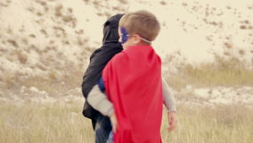 Two boys  dressed as superheroes playing in the. Two boys dressed as superheroes playing in the park outdoors stock video