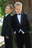 Two boys dressed in tuxedo standing near tree Stock Image