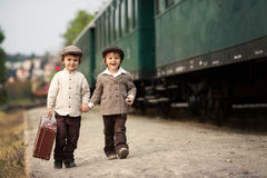 Two boys, dressed in vintage clothing and hat, with suitcase Royalty Free Stock Photography