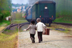 Two boys, dressed in vintage clothing and hat, with suitcase Royalty Free Stock Image