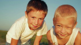 Two boys dressed in white in the park looking at. The camera and smiling in the sunlight,  video stock footage