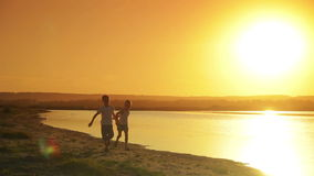 Two boys dressed in white running along the shore. Of the lake on the background of the water and sunset  silhouettes stock video footage