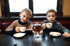 Two boys drink tea. At table in cafe stock photos