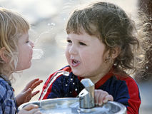 Two boys by the drinking fountain. Two cute brothers having fun outdoors Stock Photo