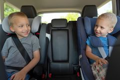 Two boys are driving in car seats royalty free stock image