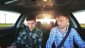 Two  boys driving in the car, speaking, speed, lifestyle. In full HD stock video footage