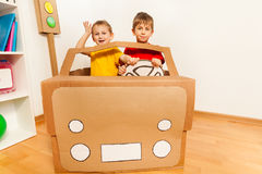 Two boys driving toy handmade cardboard car. Two happy friends, five years old boys, driving toy handmade cardboard car at the kindergarten class Stock Image