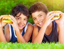 Two boys eating burgers royalty free stock photos