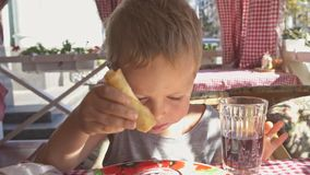 Two boys are eating pancakes for breakfast on the balcony. Sunny morning stock video