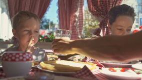 Two boys are eating pancakes for breakfast on the balcony. Sunny morning stock video footage