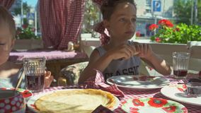 Two boys are eating pancakes for breakfast on the balcony. Sunny morning stock footage