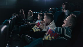 Two boys are eating popcorn in the cinema. The little boys are laughing and smiling stock footage