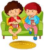 Two boys eating popcorn on sofa Royalty Free Stock Photo