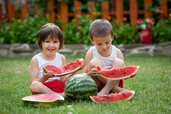 Two boys, eating watermelon in the garden, summertime Royalty Free Stock Photos